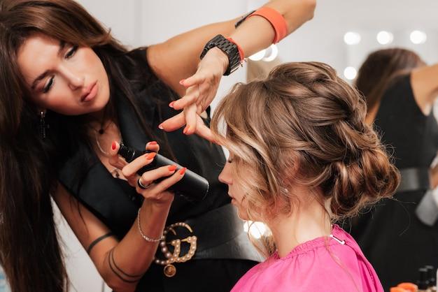 Девушка-парикмахер делает прическу клиентке к торжеству, заколачивая пряди шпильками и шпильками.
