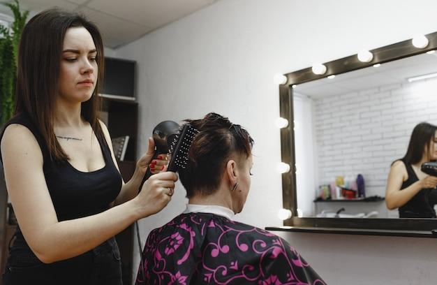 女の子の美容師は、現代の美容院で女性のクライアントのためにヘアスタイルを作ります。理髪の芸術。
