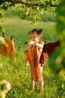 自然の中で物干しに洗った後、女の子が衣類を干して乾かします