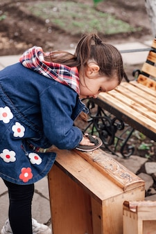Девушка помогает шлифовать старый деревянный комод рулоном наждачной бумаги, перерабатывая винтаж ...