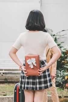 Девушка, скрывающая подарок за сюрпризом, за спиной