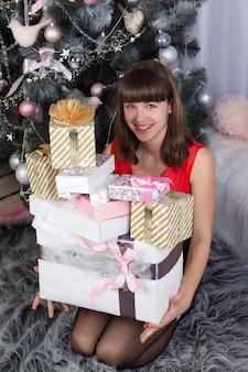 Девушка держит в руках много новогодних подарков и улыбается в комнате, украшенной к рождеству