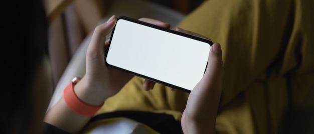 リビングルームの肘掛け椅子に足を組んで座っている間、水平方向のスマートフォンを保持している女の子