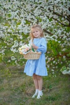 開花木の近くの花のバスケットを保持している女の子
