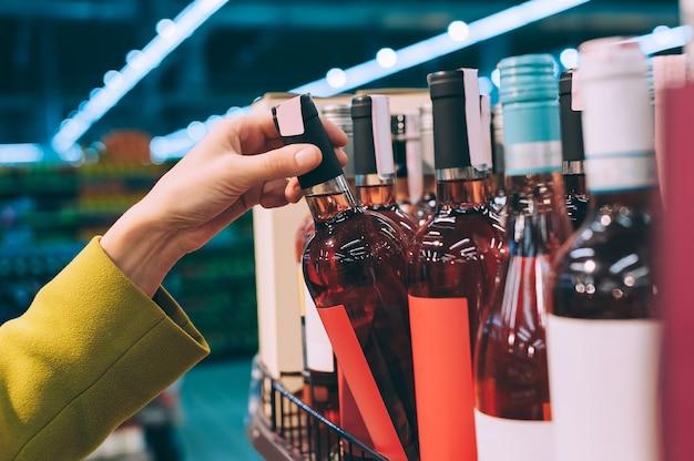 Девушка держит в магазине бутылку вина.