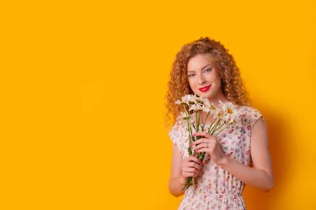 女の子は黄色のヒナギクの花束を保持しています
