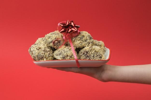 소녀는 빨간색 배경에 리본으로 묶인 수제 쿠키 그릇을 보유하고 있습니다. 맛있는 신선한 집에서 만든 사탕.