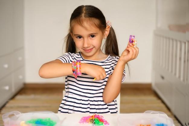 女の子は輪ゴムからブレスレットを織るための織機を持っています