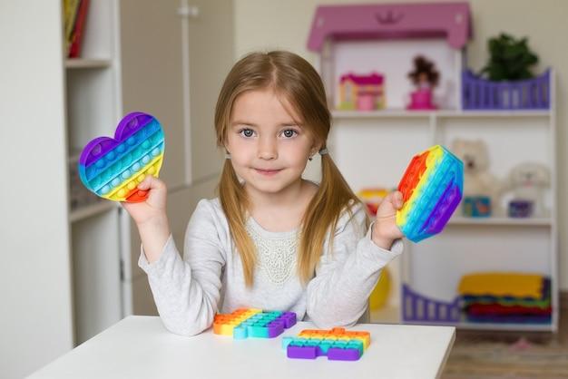 女の子は彼女の手でポップイットおもちゃを持っています