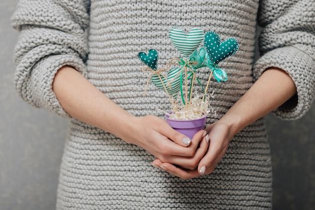 Девушка держит горшок с самодельными зелеными сердечками на деревянных палочках. концепция цветы в форме сердца.