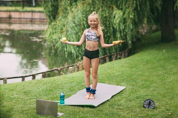 Девушка держит в руке яблоко и банан после онлайн-тренировки на природе