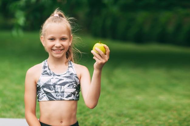 Девушка держит в руке яблоко после онлайн-тренировки на природе