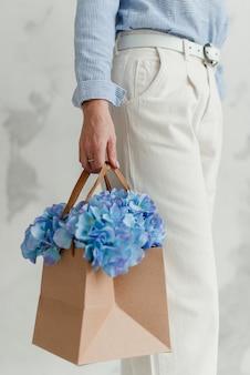 女の子は花を持っています。ギフトボックスの装飾的な花。配達付きの花。アートフラワー。