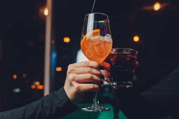 Девушка держит в руке прозрачный бокал красного коктейля, в бокале плавают кубики льда.