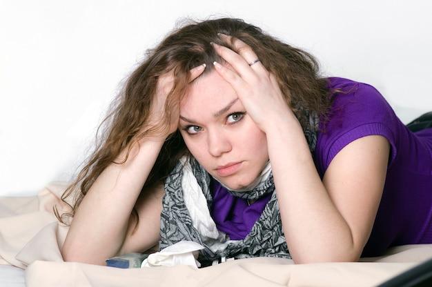 Девушка держится за больную голову во время болезни