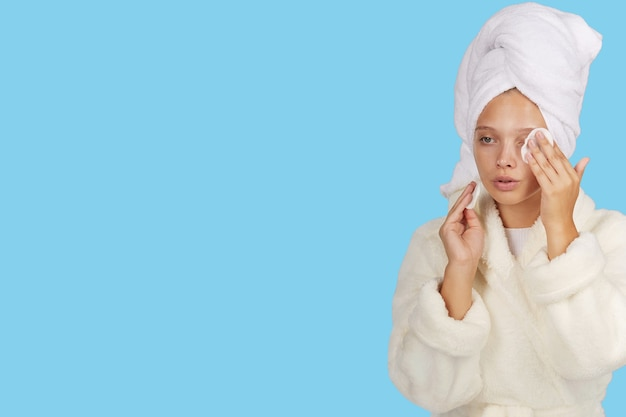 バスローブを着た女の子が、隔離された場所でシャワーを浴びた後、コットンパッドで肌をきれいにします