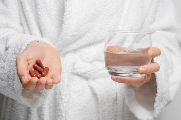 목욕 가운을 입은 소녀가 약, 캡슐 및 물 한 잔으로 약을 먹을 준비를하고 있습니다.