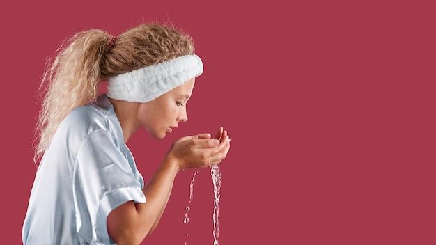 バスローブを着た女の子が孤立した上で水で洗う