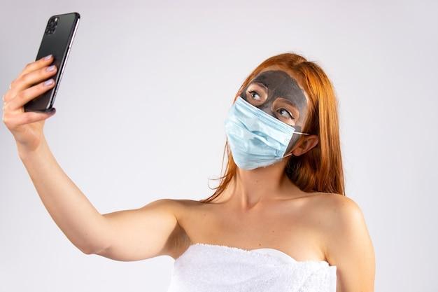 Девушка в салоне красоты с косметической маской на лице и другой лечебной. делает селфи. красота, спа, здоровье и концепция covid 19. фото высокого качества
