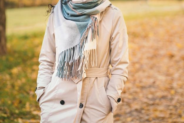 베이지색 망토를 입은 소녀가 가을 공원을 산책하며 소녀는 가을 날씨 배경을 즐깁니다...
