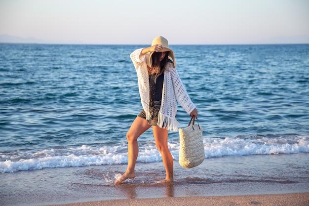 籐のバッグを持った大きな帽子をかぶった女の子が海岸を歩きます。夏休みのコンセプト。