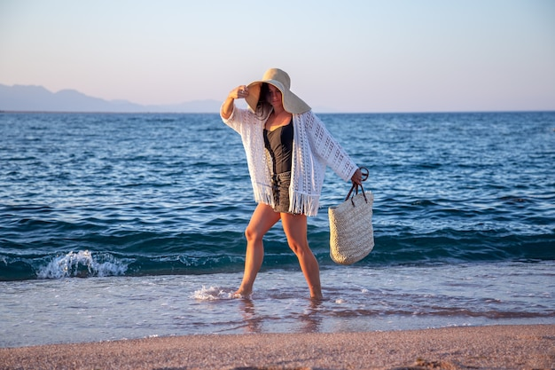 큰 모자를 쓴 소녀와 고리 버들 가방이 해변을 걷고 있습니다. 여름 휴가 개념.