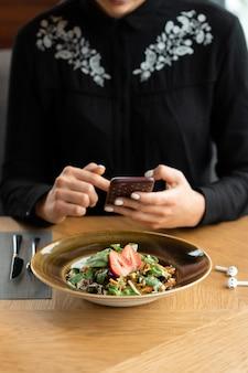 검은 블라우스를 입은 소녀가 레스토랑에서 스마트 폰으로 음식을 촬영합니다. 신선한 딸기와 함께 garnished 야채 샐러드. 필드의 얕은 깊이, 배경을 흐리게.