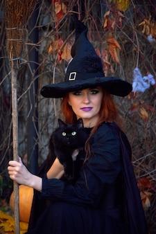 公園で黒い猫とハロウィーンの黒いドレスと魔女の帽子の女の子