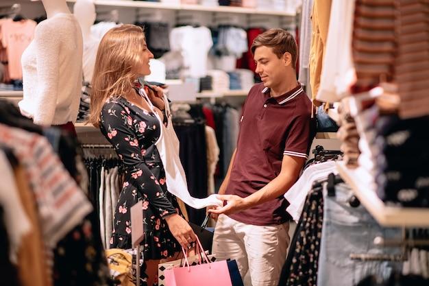 バッグを手にした花の黒いドレスを着た女の子が白いtシャツを試着し、バーガンディのtシャツとベージュのパンツで彼氏をどのように見るかを示します。服の選択