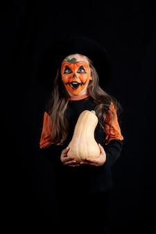 Девушка в черной шляпе и с тыквенным макияжем на лице держит тыкву в руках и празднует хэллоуин, изолированно