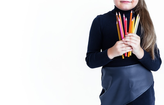 Девушка в черной куртке и юбке держит в руках цветные карандаши