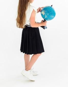 Девушка в черной юбке и белой блузке держит в руках глобус и стоит спиной к камере.