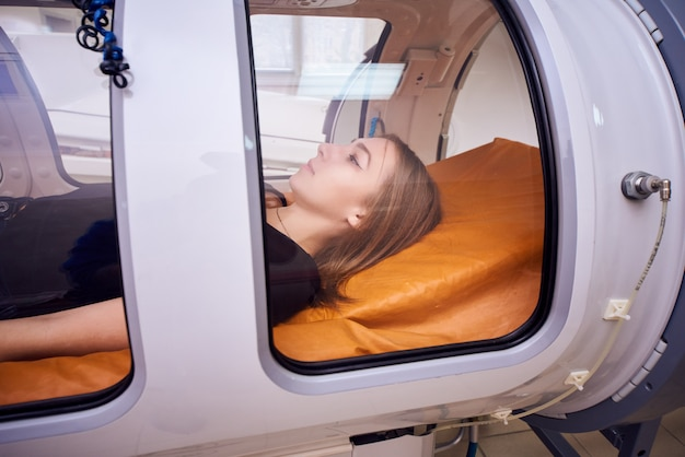 Девушка в черной футболке лежит в гипербарической камере, кислородная терапия