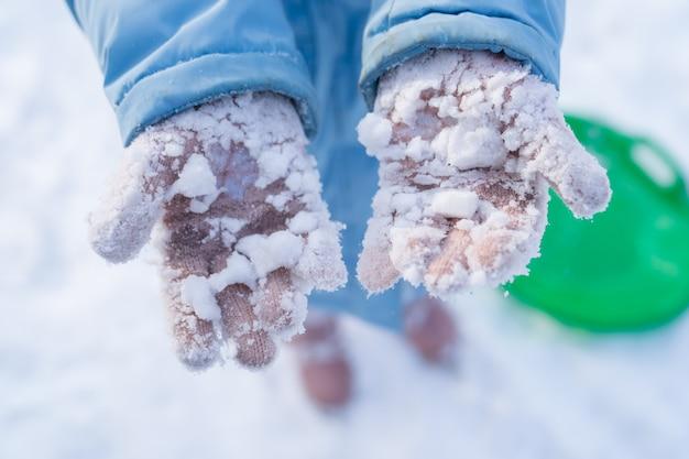Девушка в синем пальто показывает снег, прилипший к розовым перчаткам после игры в снежки.