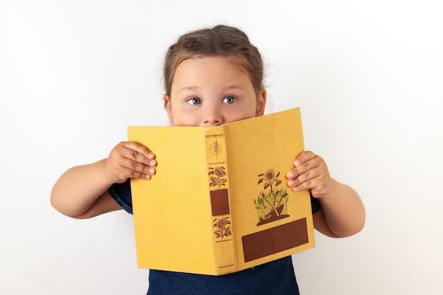 Девушка в синем джинсовом платье держит перед лицом оранжевую книгу и прячется за ней. веселый ребенок, изолированный.