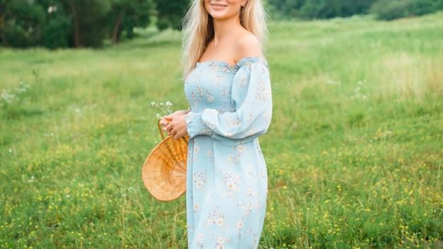 青いドレスの少女は花のバスケットを持っています