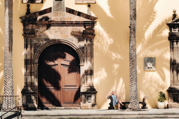 Девушка в синем платье сидит на скамейке в старом городе гарачико на острове тенерифе в солнечный день. турист гуляет по старому городу на острове тенерифе, канарские острова. испания.