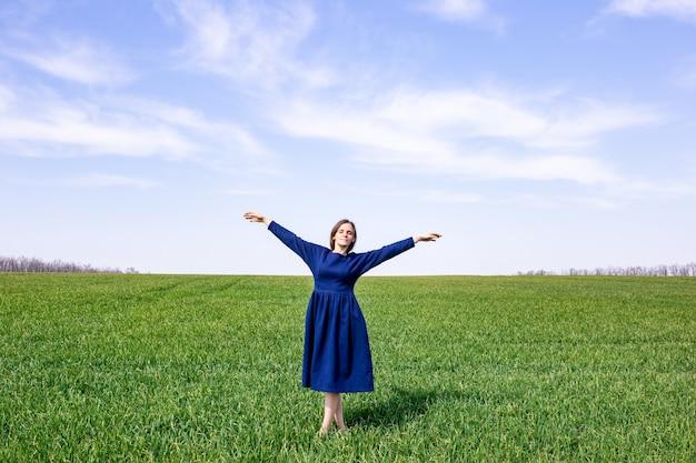 푸른 드레스를 입은 소녀가 푸른 밀밭에 서 있습니다. 봄 풍경입니다. 농업.