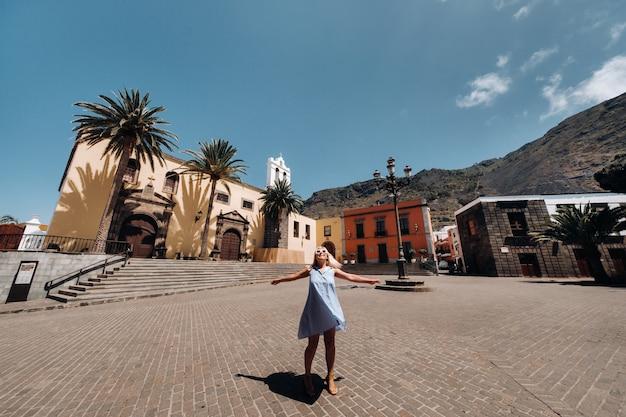 Девушка в синем платье гуляет по старому городу гарачико на острове тенерифе в солнечный день. турист идет по старому городу тенерифе на канарских островах. испания.