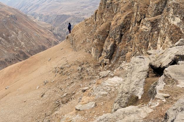 Девушка в синем пиджаке и бордовых джинсах стоит на краю горы среди песчаного каньона