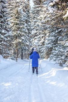 파란 재킷을 입은 소녀가 겨울에 눈 덮인 숲에서 스키를 타러 간다.