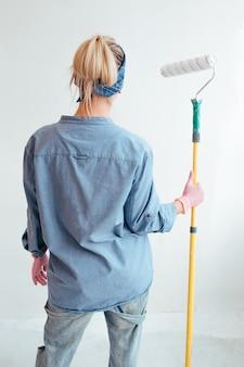 Девушка в синей рубашке и джинсах держит валик для покраски стен