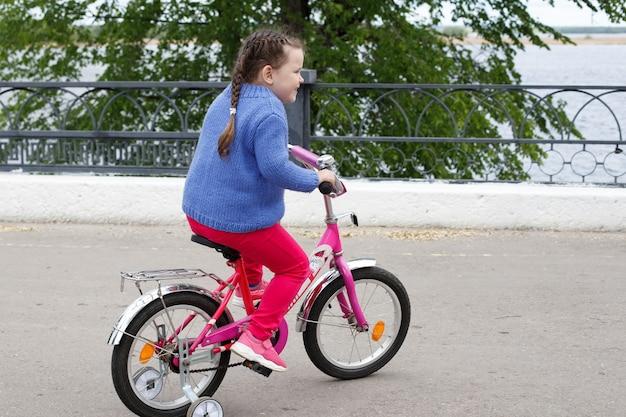 青いセーターとピンクのパンツを着た女の子が、川沿いのピンクの自転車に乗っています。