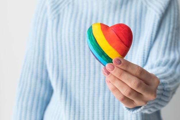 Девушка в синем свитере держит в руках разноцветное сердце, концепция лгбт-дружбы.
