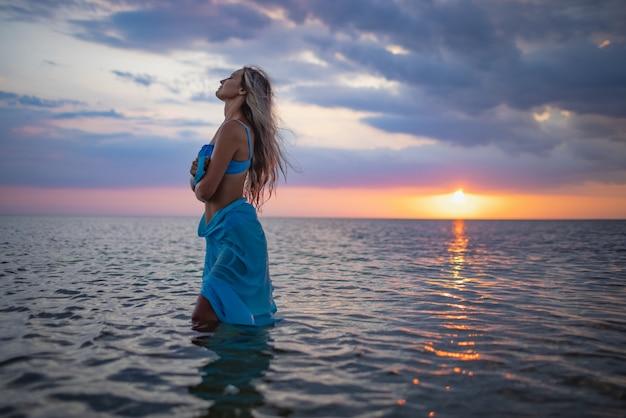 파란 수영복을 입은 소녀와 투명한 물이 있는 강어귀의 일몰을 배경으로 포즈를 취한 밝은 파레오