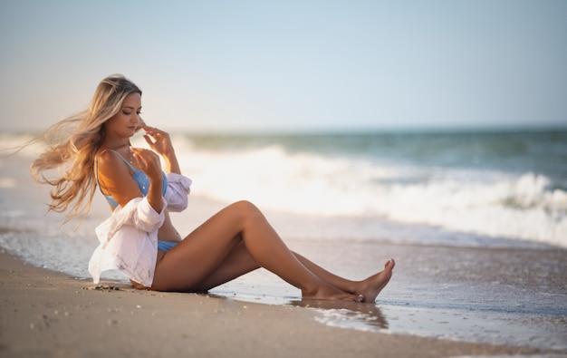 푸른빛이 도는 수영복과 셔츠를 입은 소녀가 물가 근처에 앉아 수평선을 들여다본다