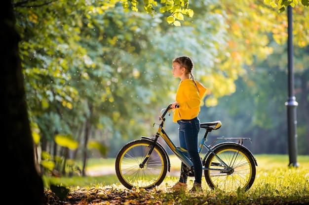 晴れた日に秋の公園で明るい黄色のスウェットシャツを着た女の子が自転車に乗る。
