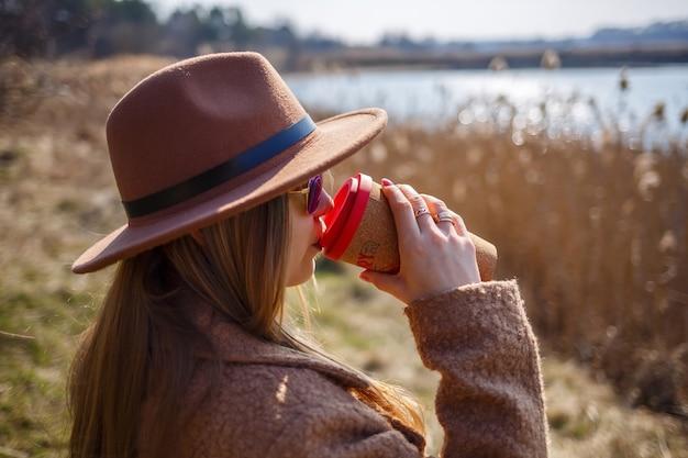 갈색 코트, 모자, 안경을 쓴 소녀가 밝은 태양 아래 호수가 있는 공원을 걷고 있습니다. 종이컵으로 차를 마시는 것. 봄의 시작