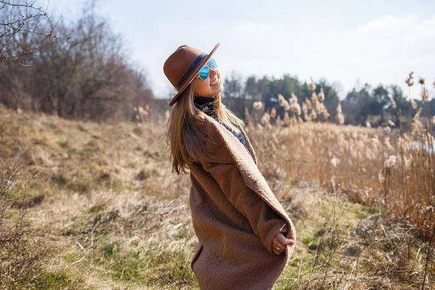 茶色のコート、帽子、眼鏡をかけた女の子が、明るい太陽の下で湖のある公園を散歩します。人生と笑顔で喜びます。春の始まり