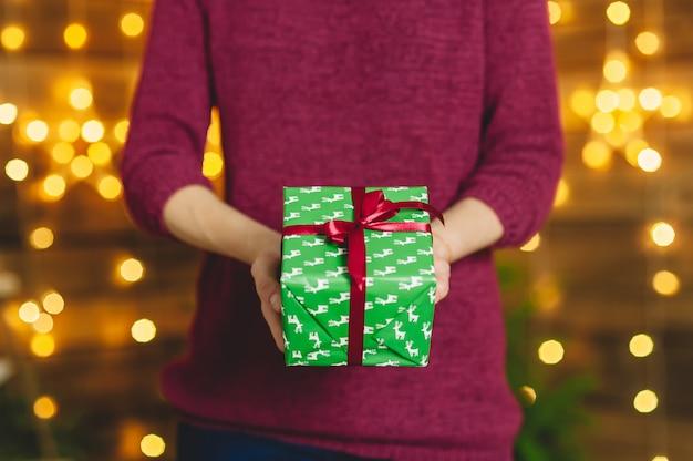 와인 색 스웨터에 여자는 그녀의 손에 빨간 리본 함께 녹색 상자 선물을 보유하고있다. 백그라운드에서 별의 화환과 나무 벽이 있습니다. 휴일 테마에 개념입니다.